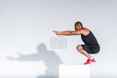 side view of young african american sportsman ready to jump on grey