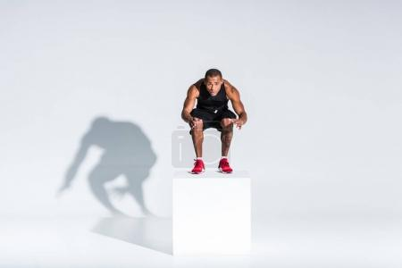Photo for Full length view of young african american sportsman jumping and looking at camera on grey - Royalty Free Image