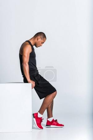 side view of young african american sportsman sitting and looking down isolated on grey