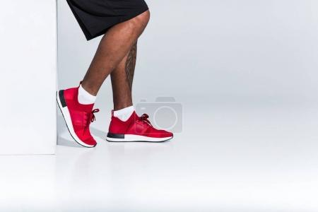 cropped shot of young african american sportsman in red sneakers on grey
