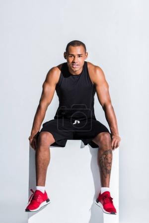 young african american sportsman in sportswear sitting and smiling at camera on grey