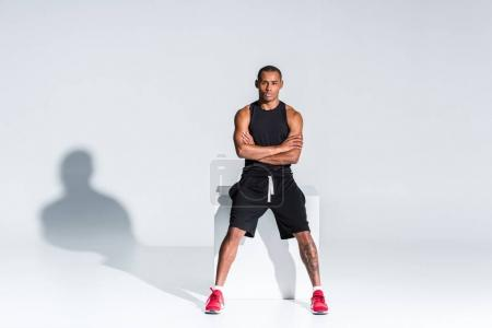 young african american sportsman with crossed arms sitting and looking at camera on grey