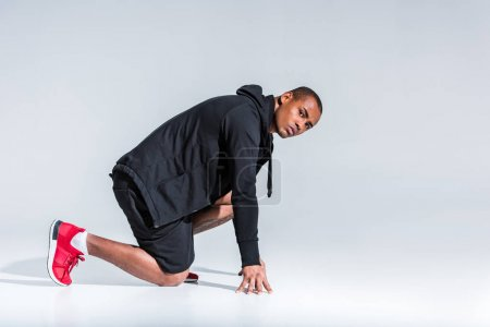 side view of young african american sportsman in hoodie ready to run and looking at camera on grey