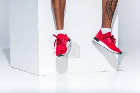 Photo for Low section of african american man in red sneakers sitting on grey - Royalty Free Image