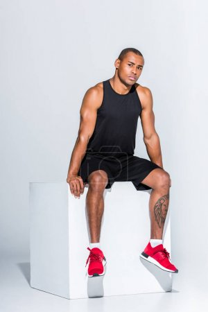 full length view of young african american sportsman sitting and looking at camera on grey