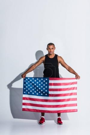 athletic african american sportsman holding american flag and looking at camera on grey