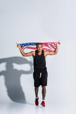 young african american sportsman holding american flag and running on grey