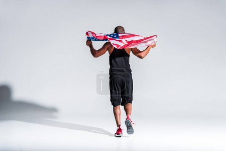 back view of young african american sportsman holding american flag on grey