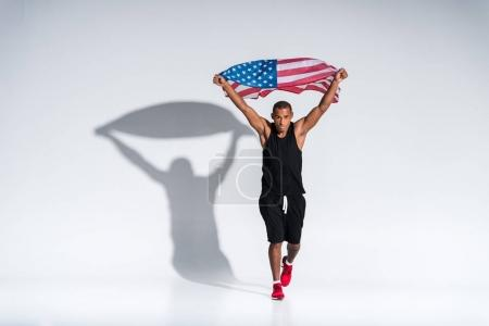 young african american sportsman with american flag looking at camera on grey