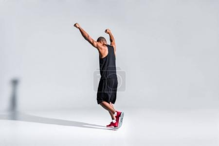 Photo for Back view of young african american sportsman triumphing with raised hands on grey - Royalty Free Image