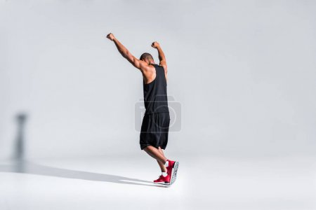 back view of young african american sportsman triumphing with raised hands on grey