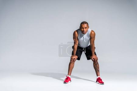 full length view of athletic young african american sportsman standing with hands on knees and looking at camera on grey