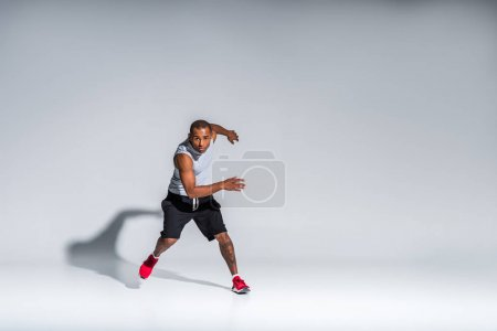 full length view of athletic young african american sportsman looking at camera on grey