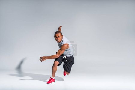 Photo for Young african american sportsman running and looking at camera on grey - Royalty Free Image