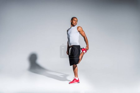 young african american sportsman stretching and looking away on grey
