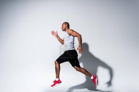 Photo for Side view of young african american sportsman running on grey - Royalty Free Image