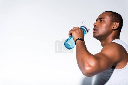 Photo for Young african american sportsman drinking water from sports bottle on grey - Royalty Free Image