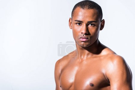 portrait of muscular sweaty african american sportsman looking at camera isolated on grey