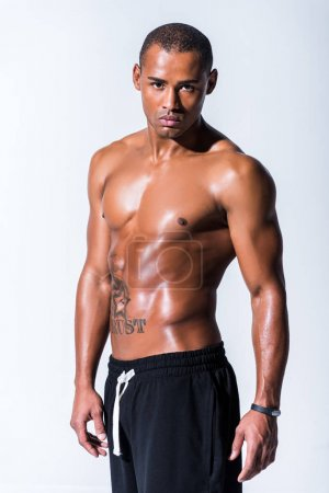athletic sweaty shirtless african american sportsman looking at camera isolated on grey