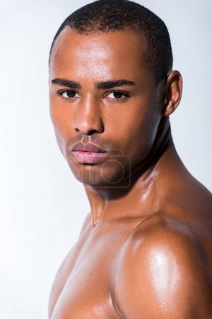 portrait of handsome shirtless african american sportsman looking at camera isolated on grey