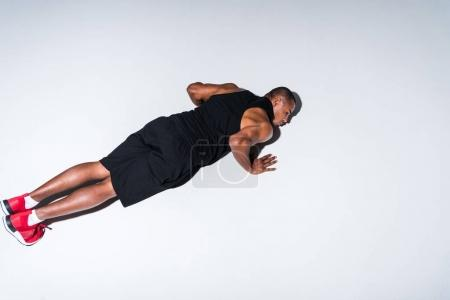 high angle view of young african american sportsman doing push ups isolated on grey