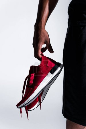 Photo for Close-up partial view of african american sportsman holding sports shoes isolated on grey - Royalty Free Image