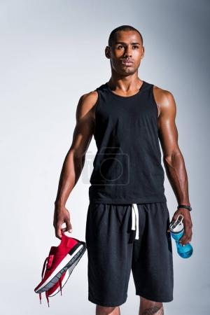 young african american sportsman holding red sneakers and bottle of water isolated on grey