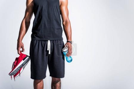 cropped shot of young african american sportsman holding red sneakers and bottle of water isolated on grey
