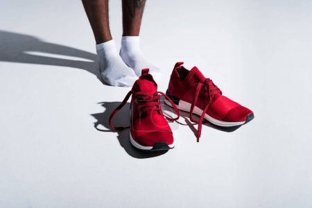 Photo for Close-up partial view of sportsman in socks and red sports shoes on grey - Royalty Free Image