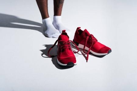 close-up partial view of sportsman in socks and red sports shoes on grey