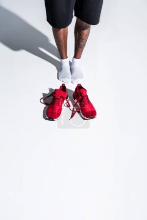 Photo for High angle view of sportsman in socks and red sports shoes on grey - Royalty Free Image