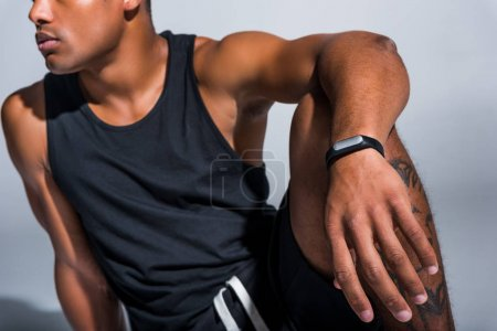 cropped shot of young african american sportsman wearing fitness tracker on grey