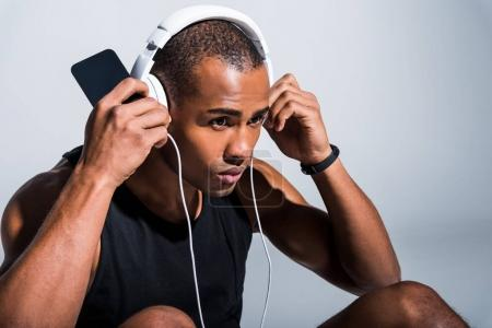 young african american sportsman in headphones using smartphone and looking away on grey