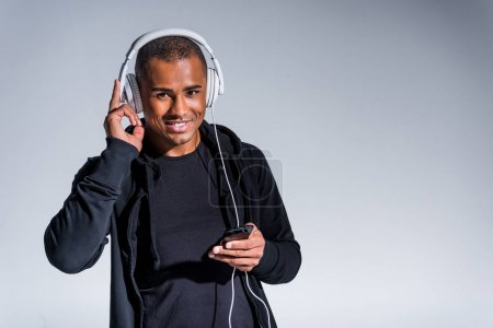 young african american man in headphones using smartphone and smiling at camera isolated on grey