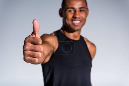 Photo for Close-up view of smiling african american sportsman showing thumb up isolated on grey - Royalty Free Image