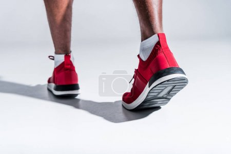 partial view of african american man in sports shoes on grey