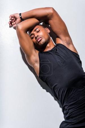 handsome young african american sportsman lying on grey