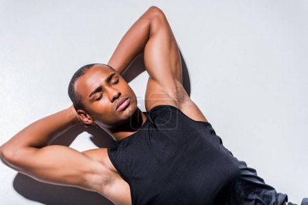 young african american sportsman with closed eyes lying with hands behind head on grey