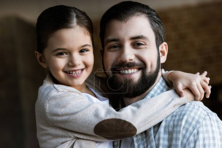 Photo for Cheerful father and daughter hugging and looking at camera at home - Royalty Free Image