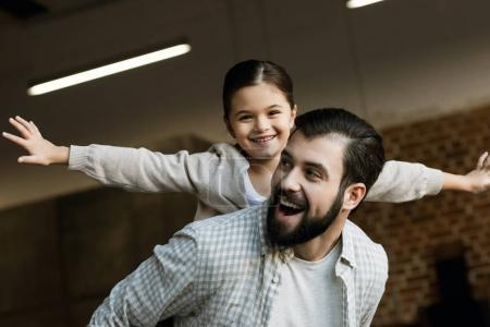 happy father giving piggy back ride to young daughter at home