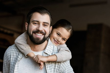 cheerful father and daughter hugging and looking at camera at home