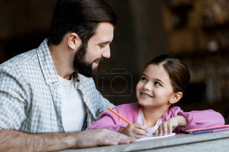 père heureux avec la petite fille assise à table et dessin dans l'album à la maison