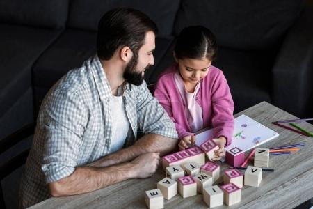 father with daughter sitting at table and making words by cubes with letters at home