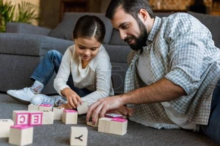 cheerful father with daughter making words by cubes with letters at home