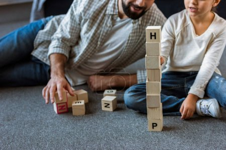 cropped image of father with daughter making words by cubes with letters at home