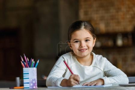 petit enfant assis à table et le dessin dans l'album à la maison