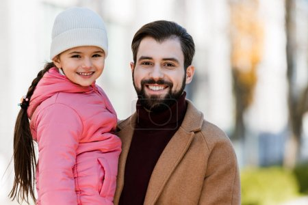 Photo for Happy father with daughter hugging and looking at camera. outside - Royalty Free Image