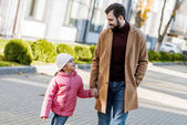 cheerful father with little daughter walking outside in autumn outfit and looking at each other. outside