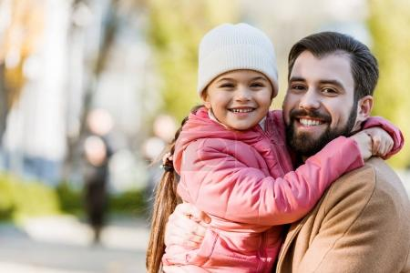 happy father with daughter hugging and looking at camera. outside