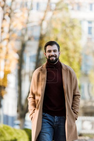smiling handsome man in autumn outfit looking at camera. outside